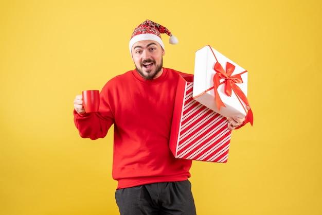 Вид спереди молодой самец с подарком на рождество и чашкой чая на желтом фоне