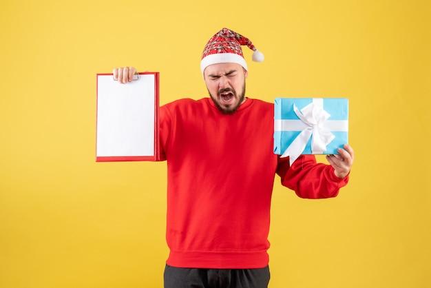 Вид спереди молодой самец с подарком на рождество и запиской на желтом фоне