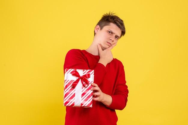 Вид спереди молодой самец с рождественским подарком на желтом фоне