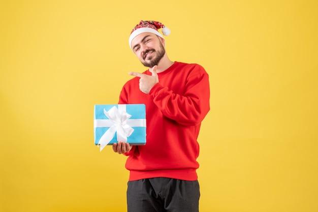 노란색 배경에 크리스마스 선물 전면보기 젊은 남성