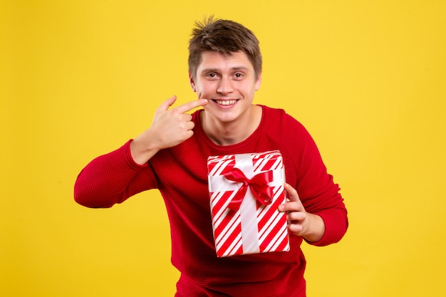 Front view young male with xmas present on yellow background