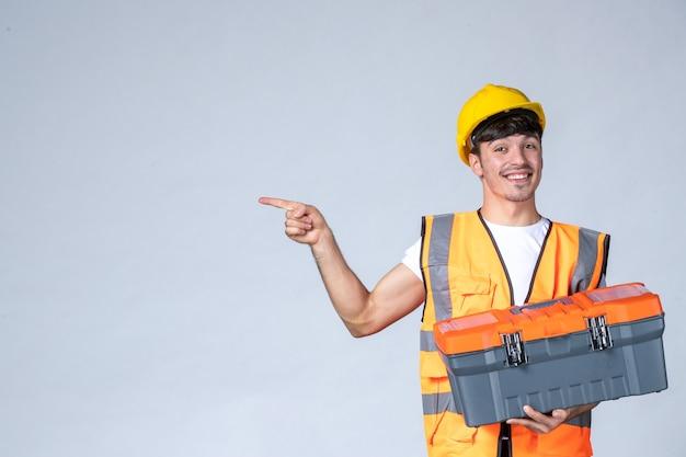 Вид спереди молодой работник мужского пола держит чемодан с тяжелым инструментом на белом фоне