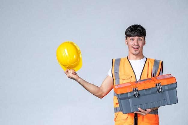 白い背景の上の重いツールケースを保持している正面図若い男性労働者