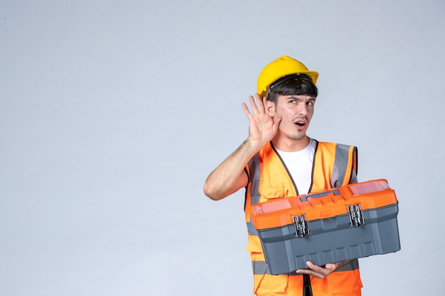 Front view young male worker holding heavy tool case on white background