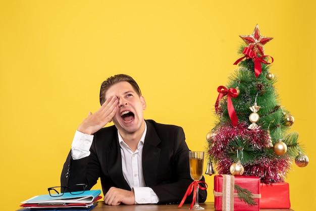 クリスマスプレゼントと木と一緒に座っている正面図若い男性労働者