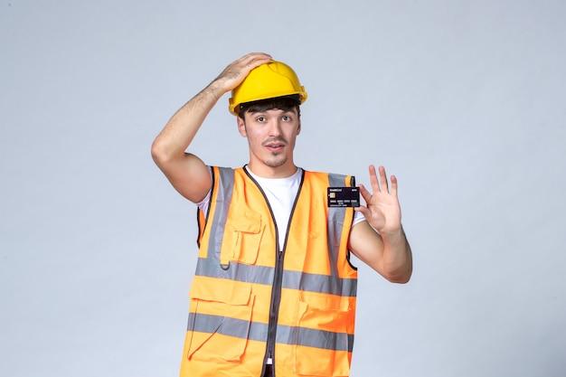 Vista frontale giovane lavoratore di sesso maschile con carta di credito nero su sfondo bianco