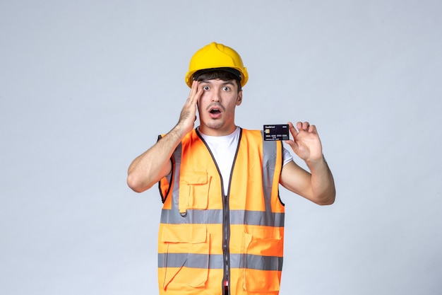 Front view young male worker with black bank card on white background
