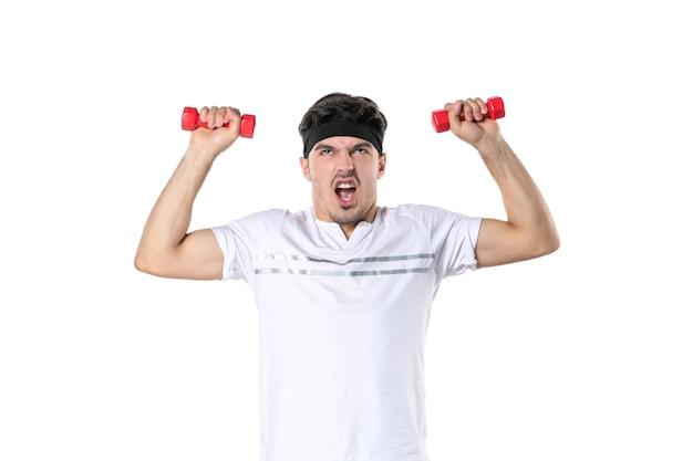 Вид спереди молодой мужчина тренируется с гантелями на белом фоне спорт цвет подходит тело йога здоровый образ жизни диета спортсмены