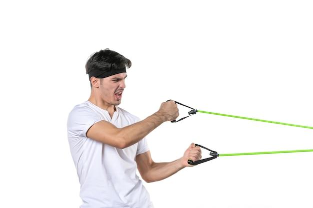 Вид спереди молодой мужчина тренируется с эспандером на белом фоне режим тела подходит спортсмен тренажерный зал тренировки диета спорт