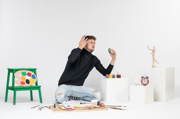正面図白い壁にペンキで作業している若い男性ペイントアートカラーアーティスト絵画写真絵を描く