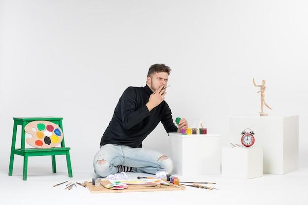 흰색 벽 아티스트 페인트 아트 컬러 페인팅 그림에 페인트로 작업하는 전면 보기 젊은 남성 그림 그리기