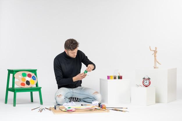 흰색 벽 아티스트 페인트 아트 컬러 페인팅 사진에 페인트로 작업하는 전면 보기 젊은 남성 그림 그리기