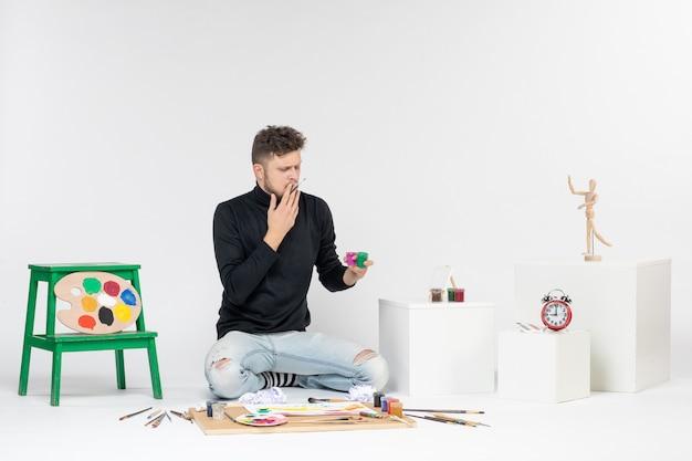 흰 벽 아티스트 페인트 아트 컬러 페인팅 그림 그리기 사진에 페인트로 작업하는 전면 보기 젊은 남성