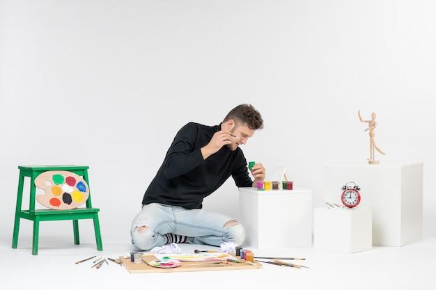 흰색 벽 페인트 아트 컬러 아티스트 그림 사진 그림 그리기에 페인트로 작업하는 전면 보기 젊은 남성