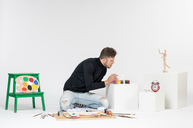흰색 벽 사진 예술 그림 그림에 페인트로 작업하는 전면 보기 젊은 남성은 색상 아티스트 페인트를 그립니다.