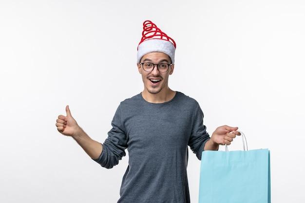 Vista frontale del giovane dopo lo shopping natalizio sul muro bianco