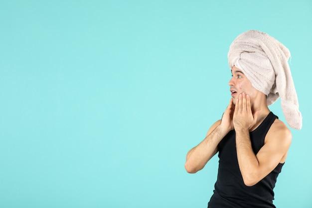 Vista frontale del giovane dopo la doccia che si applica la crema sul viso sulla parete blu