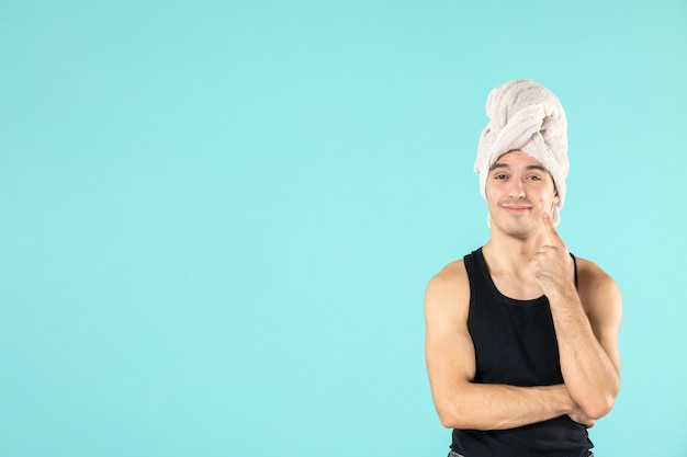 Front view of young man after shower on blue wall