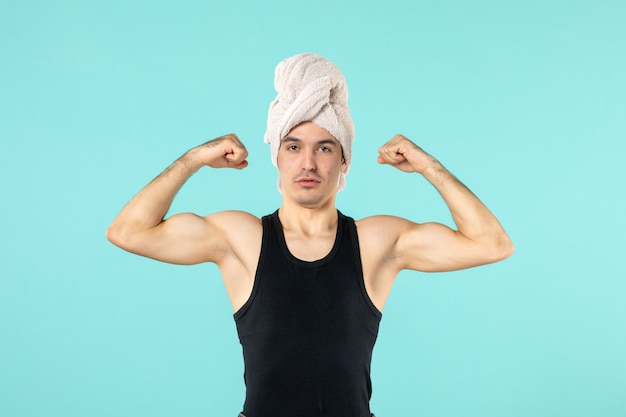 Front view of young man after shower flexing on blue wall