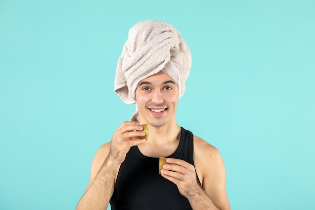 Front view of young man after shower holding kiwi slices on blue wall