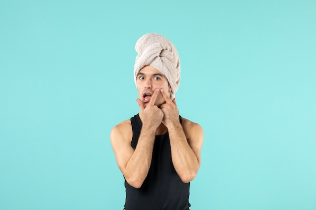Front view of young man after shower with towel on his head on blue wall