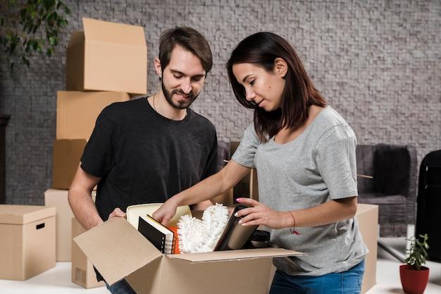 Вид спереди молодой мужчина и женщина готовятся к переезду
