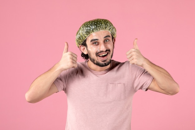 Vista frontale del giovane che si applica la maschera sul viso sul muro rosa