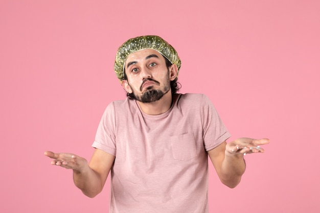 Front view of young man applying mask on his face on pink wall