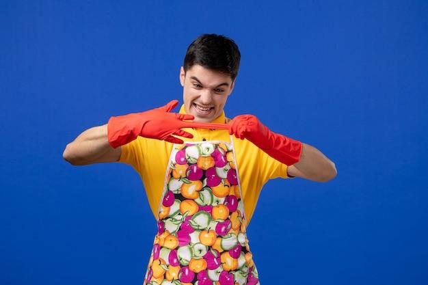Vista frontale del giovane in grembiule che si toglie i guanti sulla parete blu