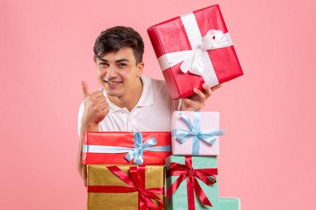 Vista frontale del giovane intorno ai regali di natale sulla parete rosa