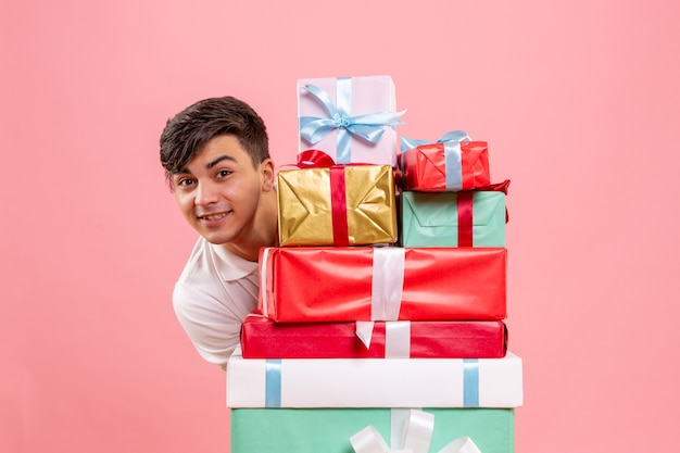 Front view of young man around christmas presents on pink wall