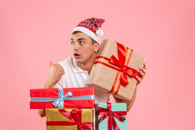 Vista frontale del giovane intorno a diversi regali di natale sulla parete rosa