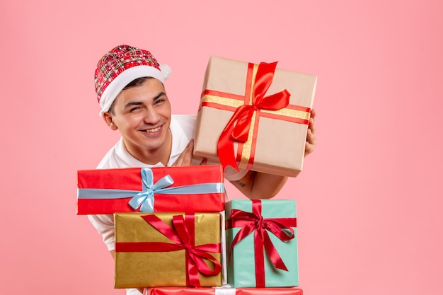 Front view of young man around different christmas presents on pink wall