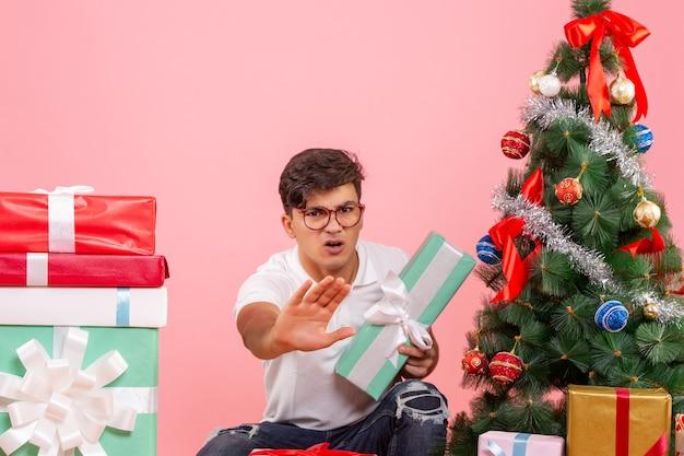 ピンクの背景にプレゼントとクリスマスツリーの周りの正面図若い男