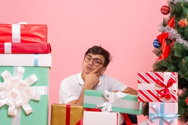 Vista frontale del giovane intorno ai regali e all'albero di natale sulla parete rosa