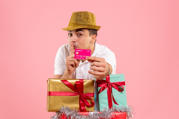 Front view of young man around xmas presents holding bank card on a pink wall