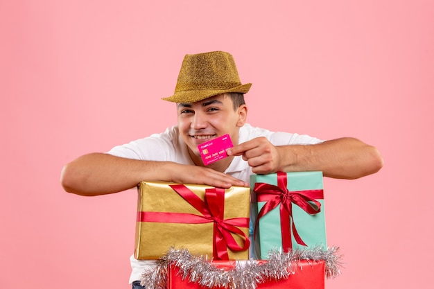 Front view of young man around xmas presents holding bank card on pink wall