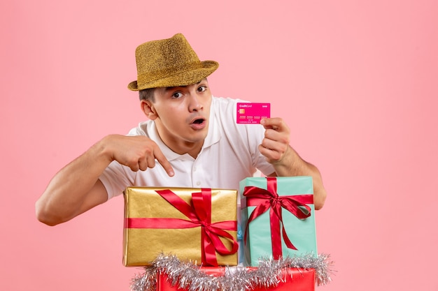 Front view of young man around xmas presents holding bank card on the pink wall