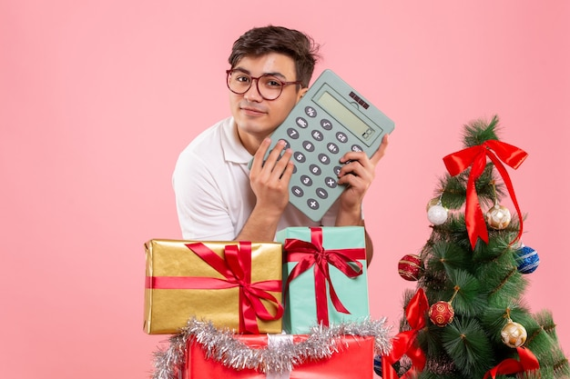 Front view of young man around xmas presents holding calculator on pink wall