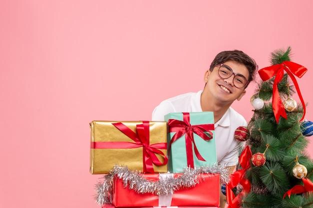 Vista frontale del giovane intorno ai regali di natale e albero di festa sulla parete rosa