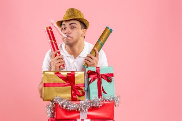 Vista frontale del giovane intorno a regali di natale con petardi sulla parete rosa
