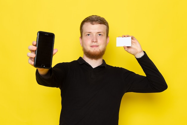 Front view of young man in black shirt holding card and phone