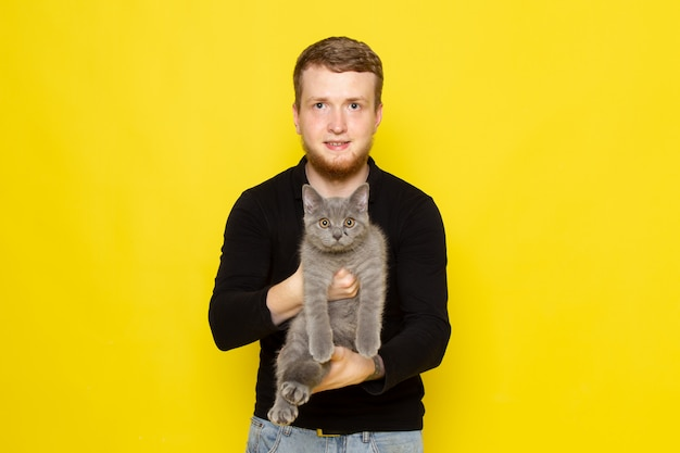 Front view of young man in black shirt holding cute grey kitten with smile