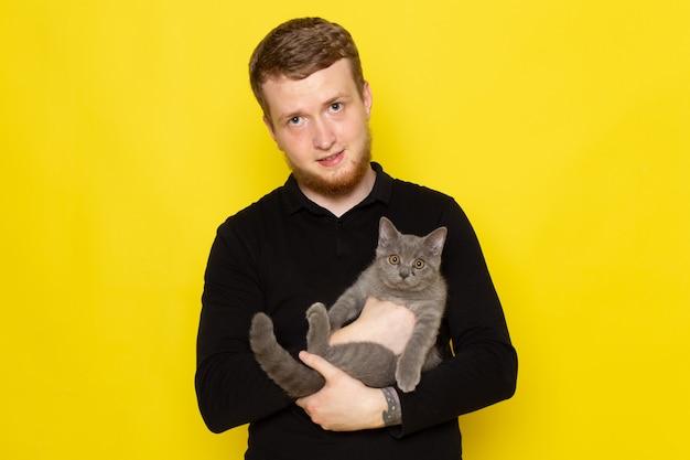 Vista frontale del giovane in camicia nera che tiene gattino grigio sveglio sulla superficie gialla