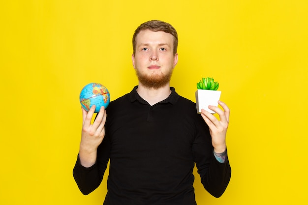 Front view of young man in black shirt holding little globe and plant
