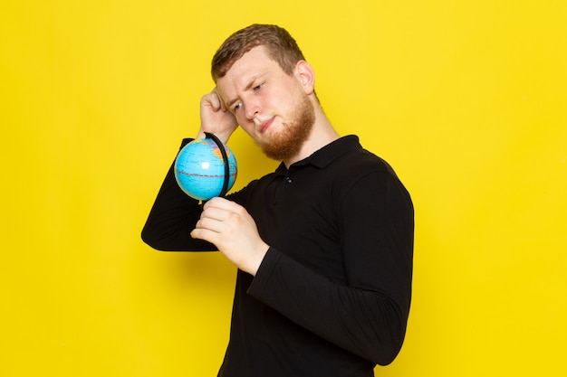 Front view of young man in black shirt holding little globe and thinking