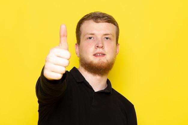 Vista frontale del giovane in camicia nera che posa mostrando come il segno
