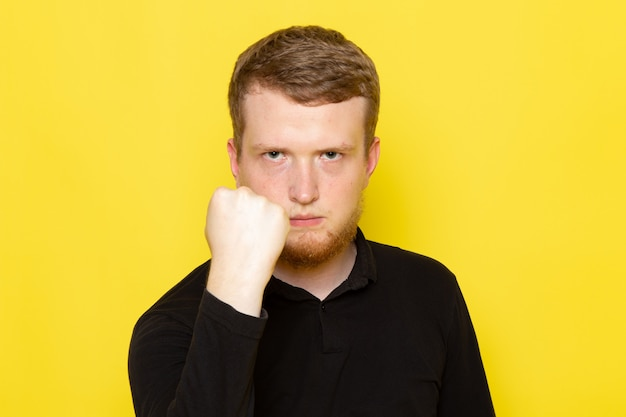 Front view of young man in black shirt posing and threatening with fist