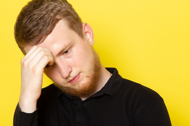 Front view of young man in black shirt posing with depressed expression