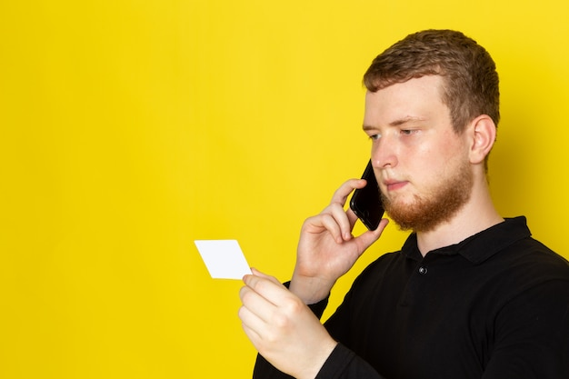 Front view of young man in black shirt talking on the phone holding white plastic card